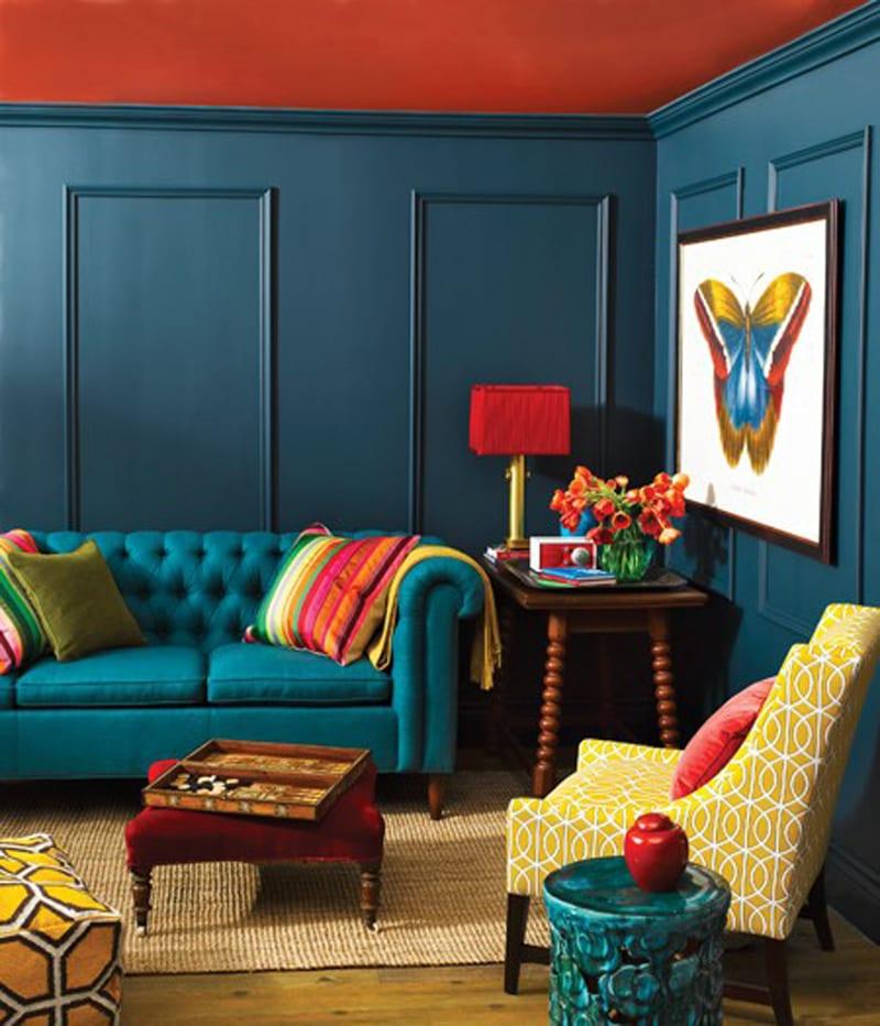 Wohnzimmer gestalten mit blauen Wänden und roter Decke-Sofa blau mit farbigen Sofadecken-polstersessel gelb-kleinmöbel aus Holz