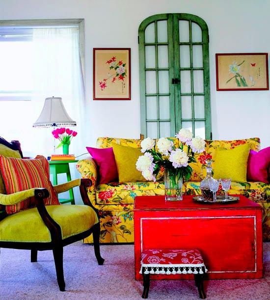 wohnzimmer mit gelbem Sofa und Holzstuhl mit gelbem Damast-kissen gelb und zyklamfarbe-roter holzcouchtisch-wandgestaltung mit grüner Bogentür