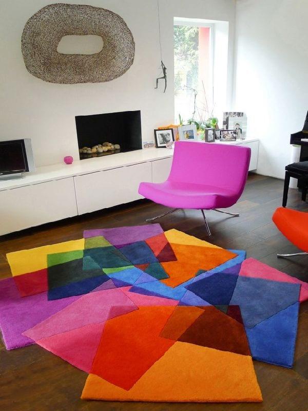 schöner wohnen farbrausch- wohnzimmer mit weißer Kommode und offenem Kamin-Sessel pink und orange-moderner teppich