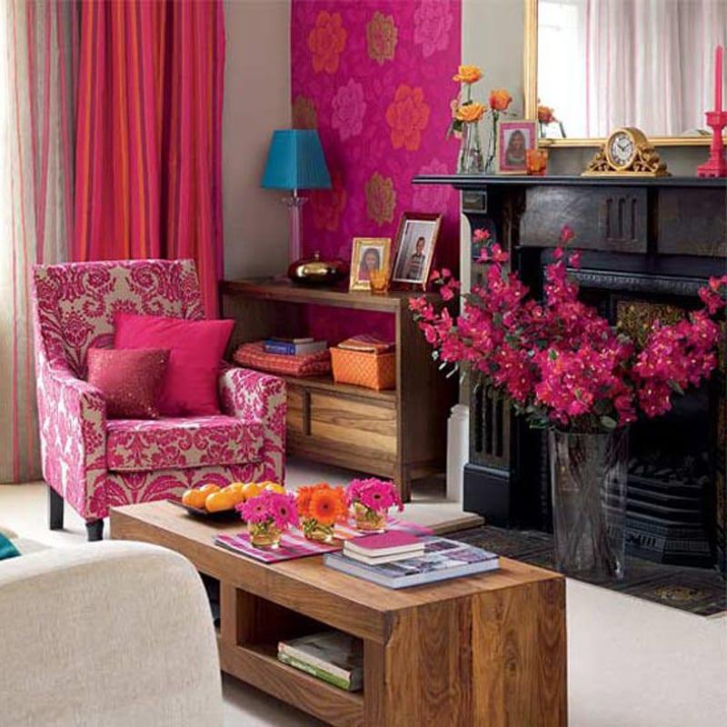 wohnzimmer mit schwarzem Kamin und Gardinen pink-weißer sessel mit  Blumenmotiven in rosa-wand tapete pink mit Blumen-kaffeetisch aus massivholz