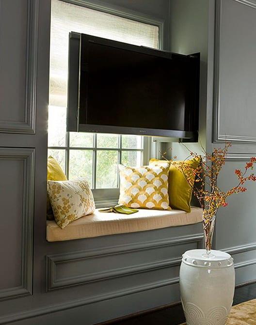 graue wandfarbe-fensterbank dekorieren mit gelben Kissen und eingebautem TV
