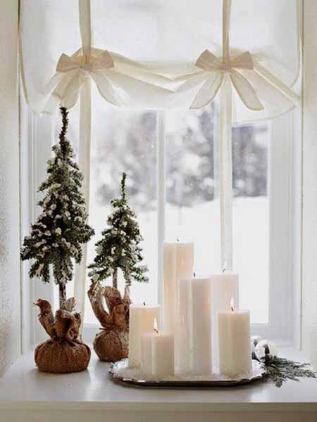 fensterdeko mit kerzen und dekorative tanenbäume