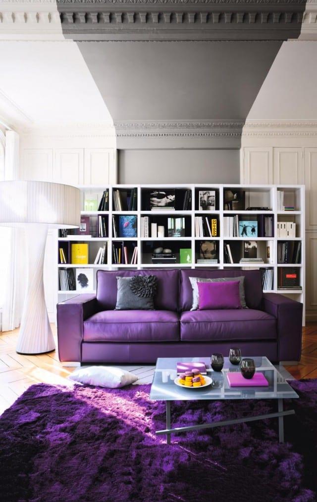 modernes wohnzimmer mit wandfarbe grau und teppich lila-polstersofa lila-wandregal weiß-moderne stehleuchte weiß