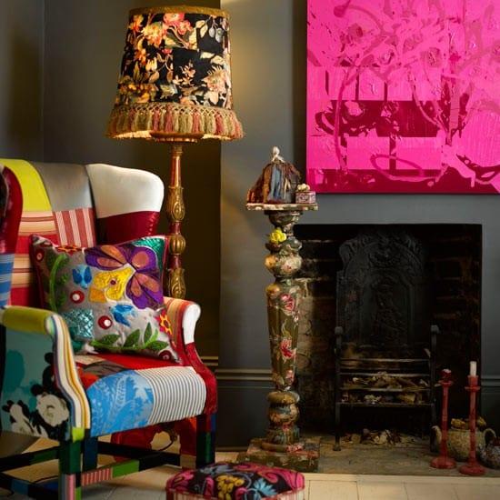 wohnzimmer gestalten mit kamin und farbigem Sessel- graue wand mit Gemälde in pink