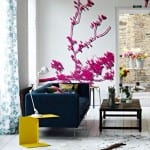 wohnzimmer gestalten mit weißem Holzboden und weißen wänden mit Wandtattoo baum in violett-polstersofa dunkelblau-nachttisch gelb-weiße Gardinen mit blauem Blumenmotiv