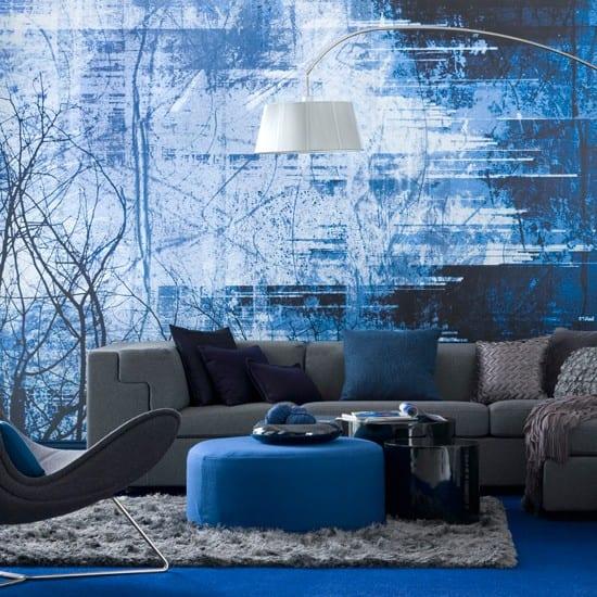 Wohnzimmer blau mit Sofa grau und rundem Polsterhocker blau-blauer Mokett mit grauem Teppich