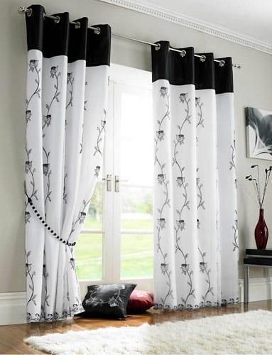 wandfarbe grautöne-weiße gardinen mit schwarzem Blumenmotiv-holzboden mit weißem teppich