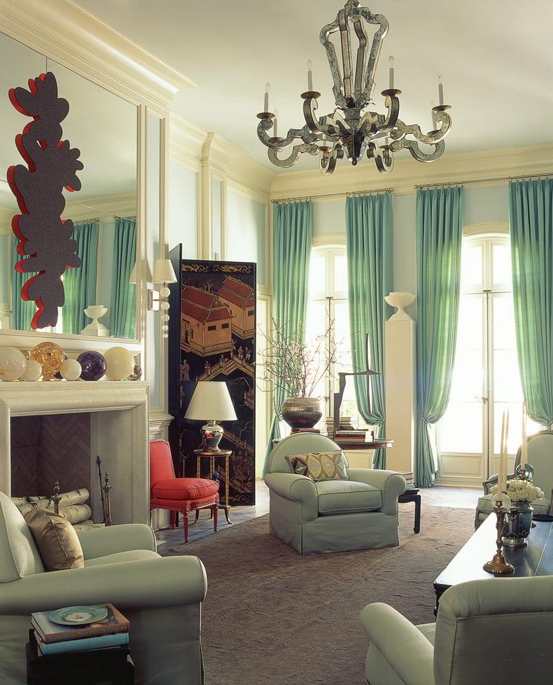 wohnzimmer gestalten mit kamin und wandspiegel-schwarze wansschirm- sessel und gardinen residagrün