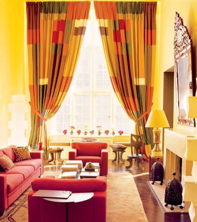 gelbe wand mit fensterdekoration gardinen gelb, rot und orange-rote sessel und sofa