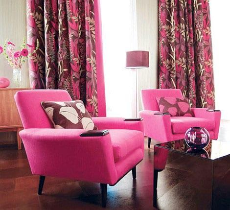 wohnzimmer einrichten in pink-dunkler Holzboden mit Vorhängen in pink und braun mit blumenmotiv-polstersessel pink-couchtisch aus schwarzem mirorglas