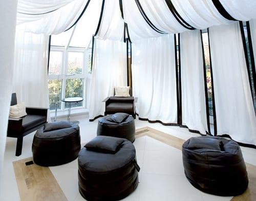 wohnzimmer gestalten mit weißen gardinen und schwarzen rundhockern