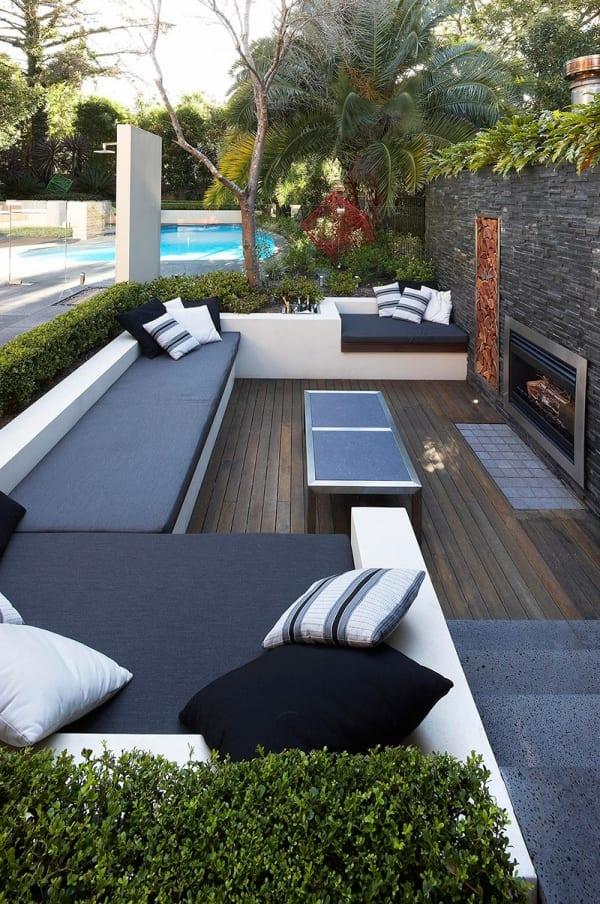terrassengestaltung mit holzboden und Gartenwand aus Naturstein mit eingebautem kamin