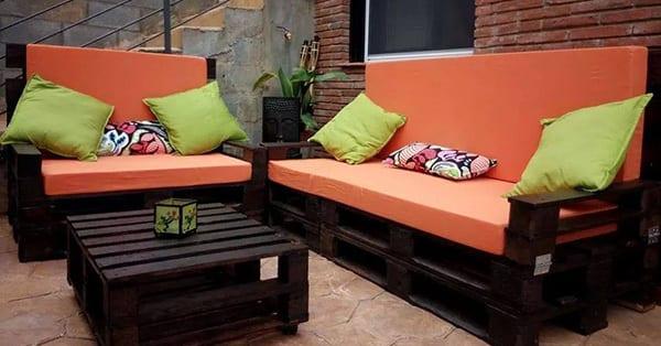 möbel aus europaletten in braun mit grünen dekokissen und orangen sitzkissen