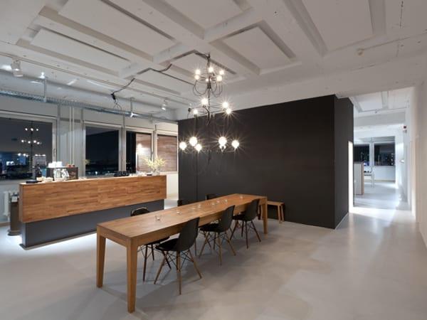 deckengestaltung mit weißen schallschutzplatten- Konferenztisch aus holz mit schwarzen stühlen