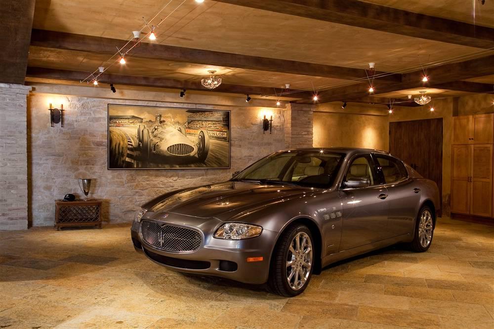 garage interior mit natursteinwand und natursteinboden-sichtbare deckenbalken-lichtgestaltung garage