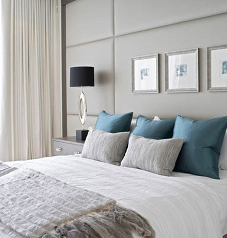 wandgestaltung schlafzimmer mit hellgrauer Polsterverkleidung und silbernen bilderrahmen-moderne dunkelblaue tischlampen