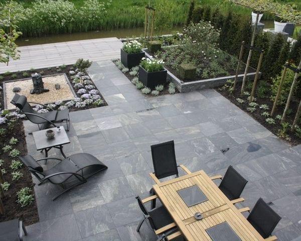 garten und landschaftsbau-terrasse mit naturstein und holzgartenmöbeln-schwarze gartenliegen