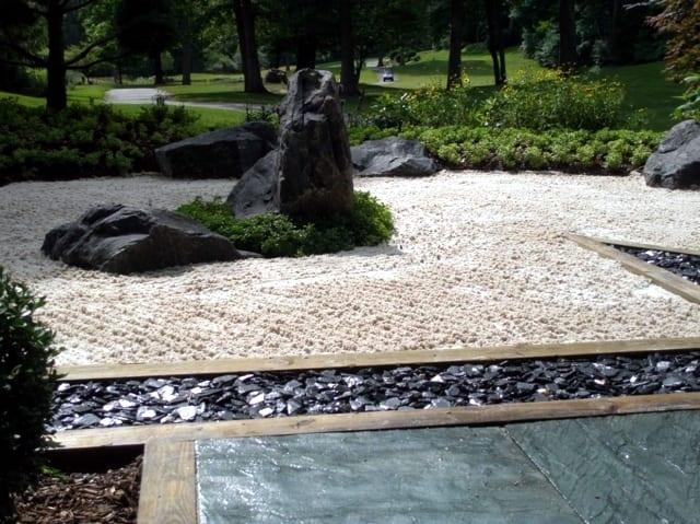 traumgarten design mit schwarzen natursteinpaltten und weißem Kies