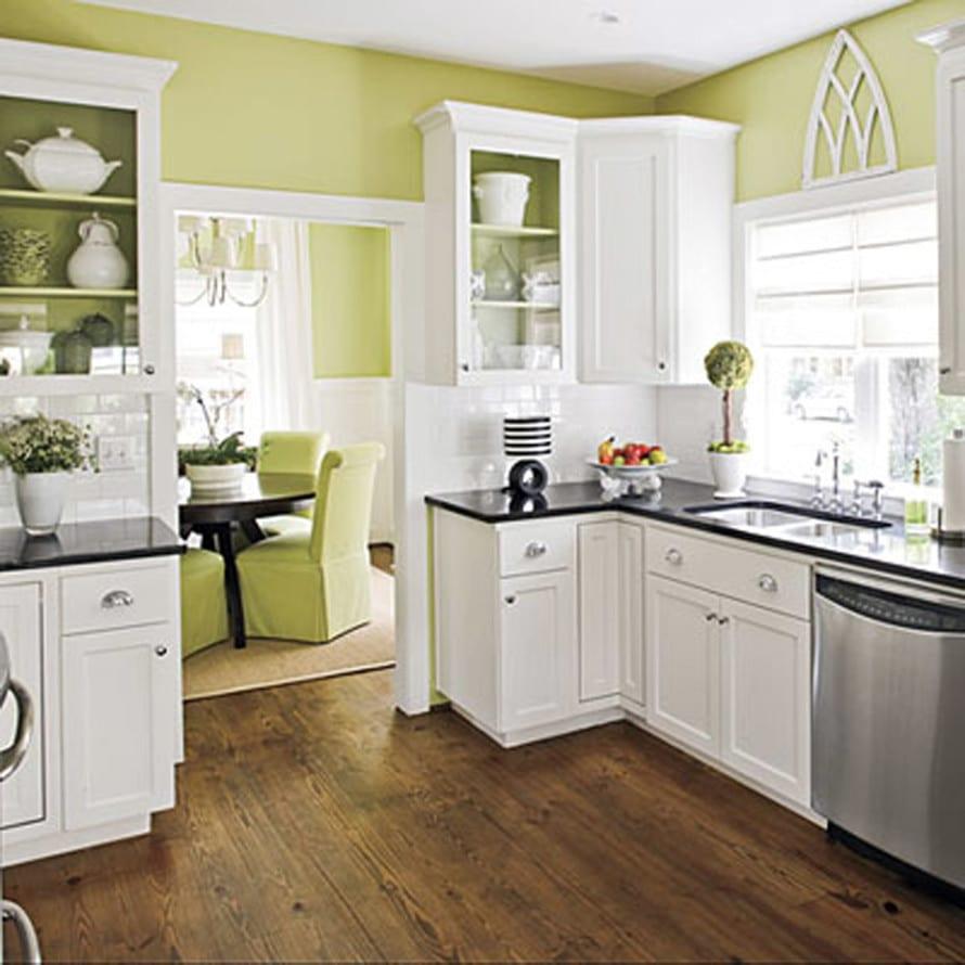 kleine küche mit weißen küchenschränken und grünen wänden
