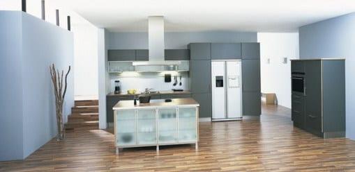 moderne küche mit Parketboden un weißen wänden-küchenschränke grau-kochinsel mit glastüren