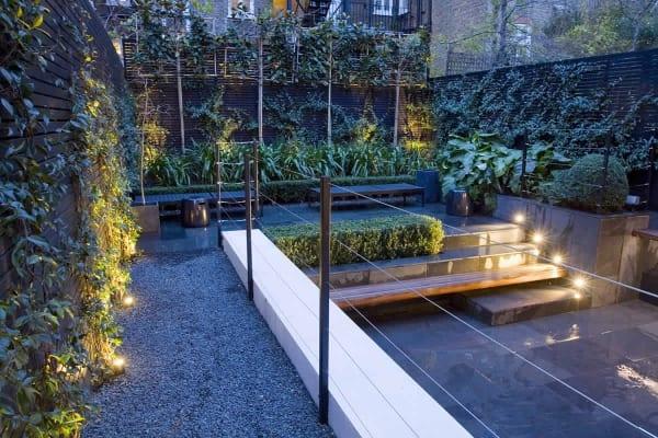 Gartenidee für Terrasse mit zwei Ebenen und Gartenmauer aus Holzbrettern und Begrünung