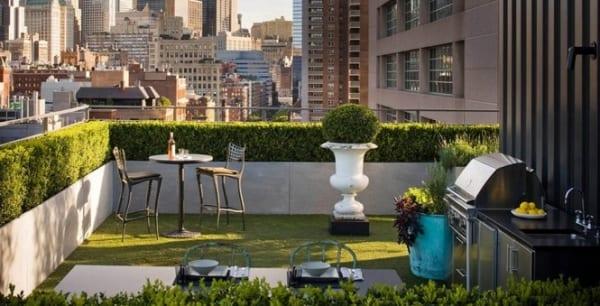 Terrassengestaltung mit Gras und Geländer aus Hecken