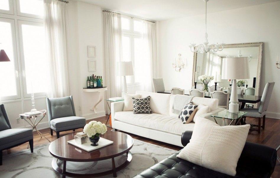wohnzimmer design mit teppich grau und ledersofa schwarz-sessel grau-rundholztisch