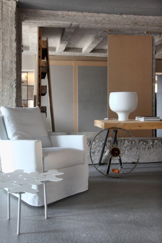 minimalistisches interior mit polstersessel weiß und designer couchtisch weiß-wandgestaltung mit Paletten