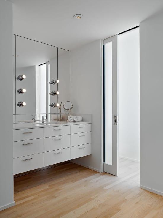 modernes badezimmer weiß mit spiegelwand und weißem waschtisch mit schubladen-innentüren weiß mit glasscheibe