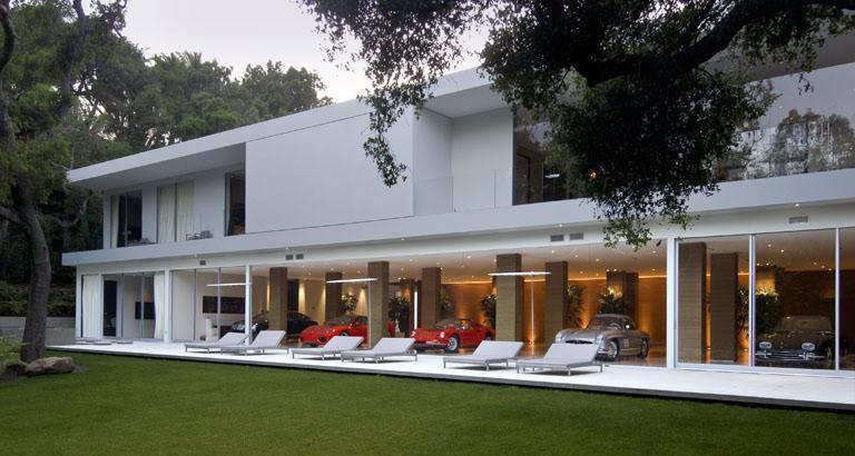 minimalistisches haus in weiß mit garten und längliche terrasse-garage mit panorama fenstern und schiebe Fenstertüren mit weißen fensterrahmen