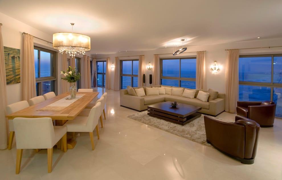 wohnzimmer einrichten mit holzesstisch und weißen polsterstühlen- ecksofa beige und ledersessel braun mit holzcouchtisch