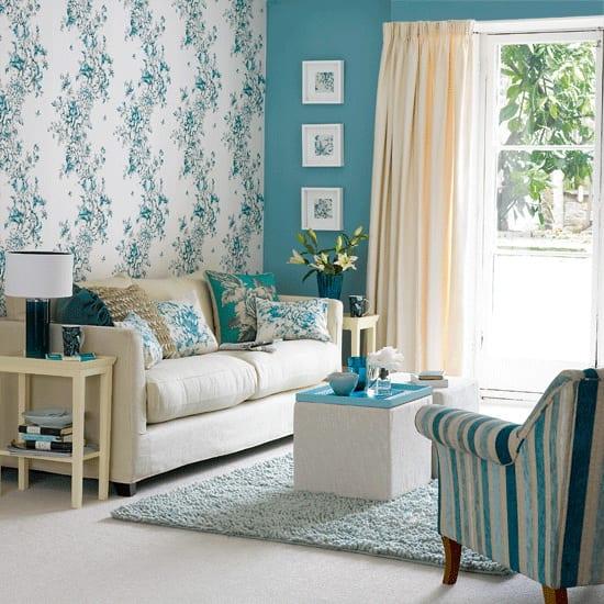 farben wohnzimmer- weiße tapete mit blauem blumenmotiv- weißes sofa mit blauen kissen- boden weiß mit weißem teppich und weißen couchtischen-sessel mit blauen und weißen streife