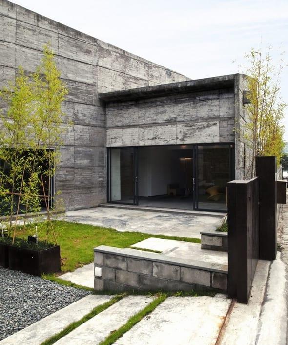 minimalistisches haus aus beton mit kleinem Vorgarten