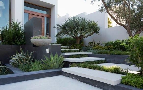 vorgartengestaltung mit schwarzem naturstein und treppe aus weißen betonplatten