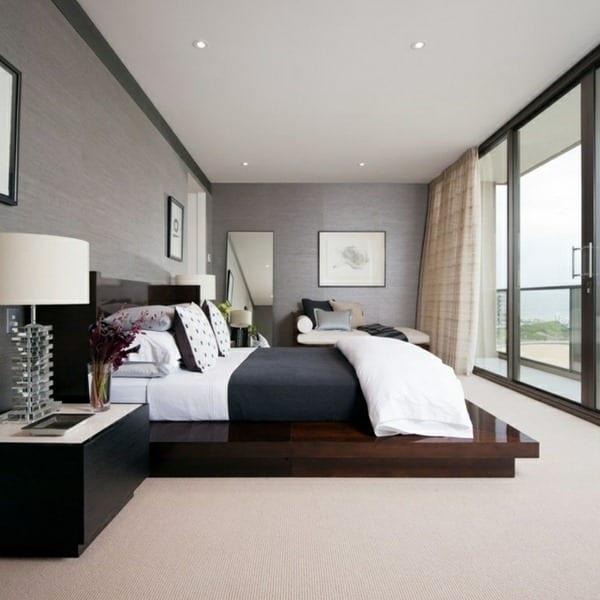 modernes schlafzimmer mit grauen wänden und holzbett mit bettwäsche grau