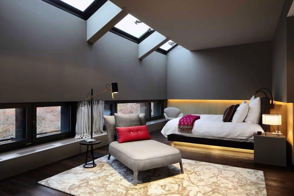 schlafzimmer dachschräge mit oberlichtern-dunkler holzboden mit teppich grau-lpolsterliege grau