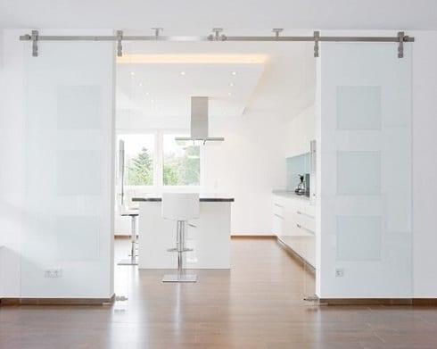 moderne küche weiß mit glasschiebetüren und kochinsel mit weißen barhockern