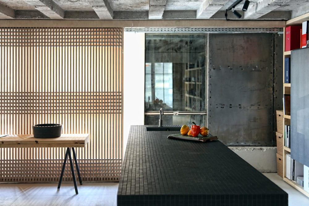 küche einrichten mit schwarzer Küchentheke und schiebbaren Gitterholzpaneelen