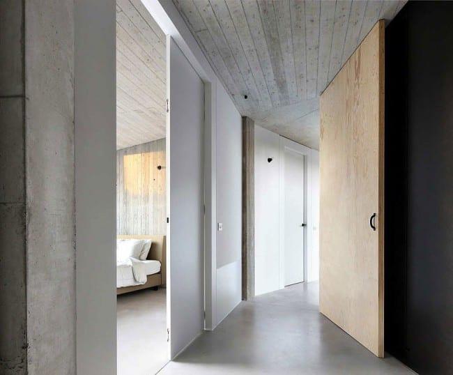 modernes haus aus beton mit dachschräge und weißen schiebetüren raumhoch