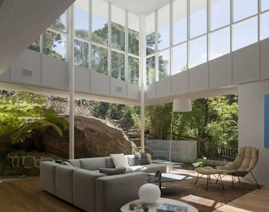 minimalistisches haus in weiß mit überdachter terrasse und steingarten-luxus wohnzimmer