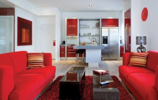 wohnzimmer mit offener Küche in rot und kücheninsel-rote sofas mit schwarzen couchtischen