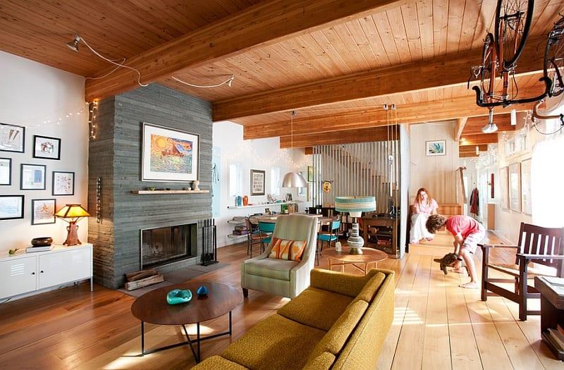 luxus wohnzimmer mit Kaminwand aus naturstein -sofa gelb-deckegestaltung mit holzverkleidung