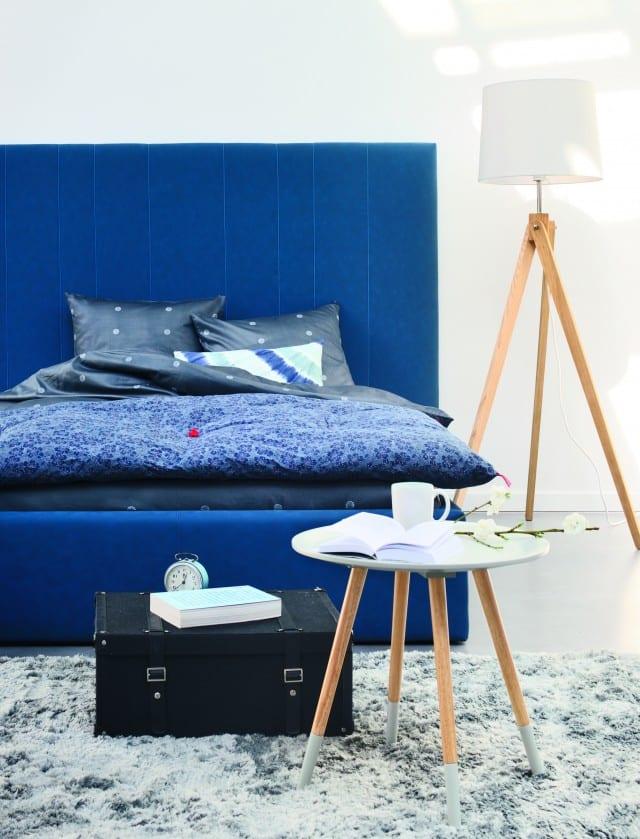 polsterbett blau mit bettwäsche blau-holzstehlampe und holzbedienungstisch
