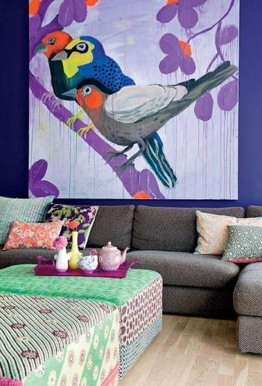 wohnzimmer gestalten mit blauer wand und grauem sofa- polster hocker in grün