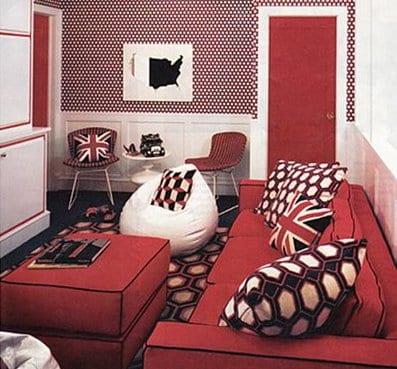 wohnzimmer mit rotem Sofa und Hocker-bodenkissen weiß-rote wand mit weißen punkten-wohnzimmertüren rot und weiße Wohnwand