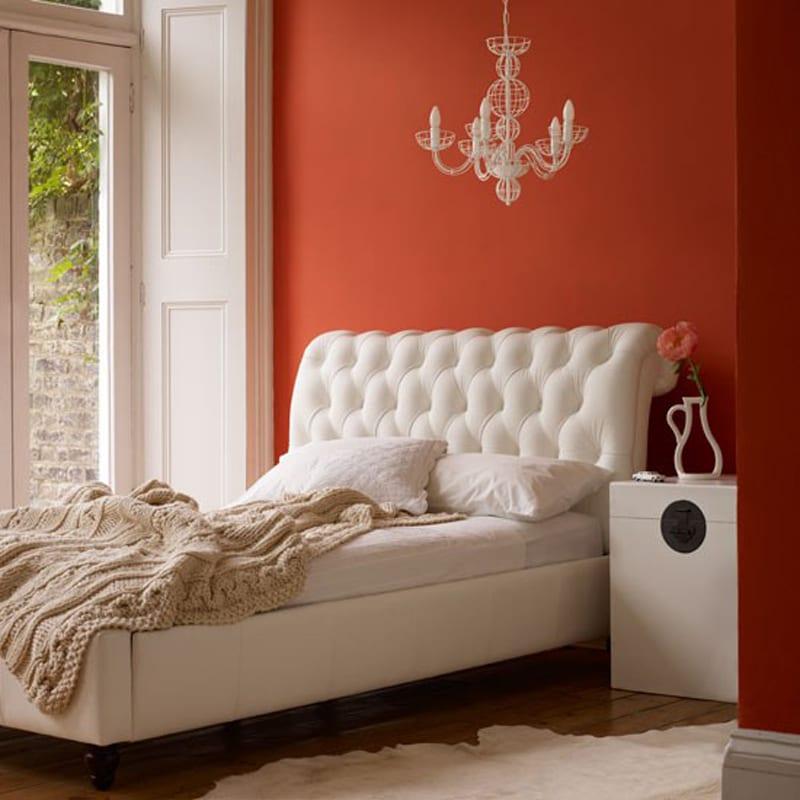 modernes Schlafzimmer mit Lederbett weiß und strickbettdecke beige