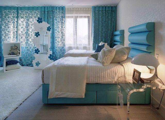 schlafzimmer mit blauem Bett und weißer bettwäsche- teppich weiß-gardinen blau