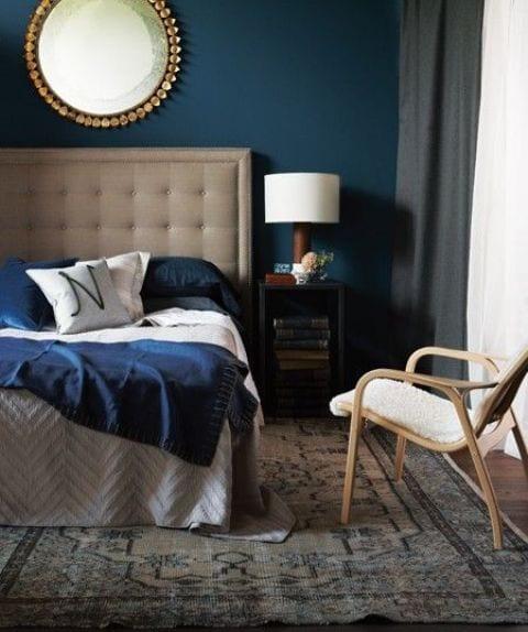 Farbgestaltung wände in dunkelblau-gardinen weiß und grau-bett mit kopgteil beige-blaue bettdecke und kissen-rundspiegel
