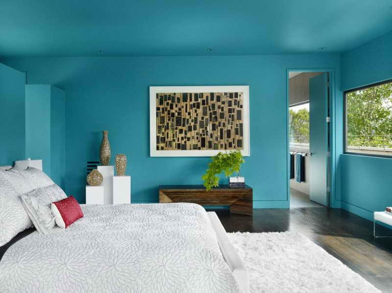 kräftige Wandfarbe blau- schlafzimmer mit dunklem Holzboden und weißem teppich-weiße bettwäsche mit blumenmotiv in grau