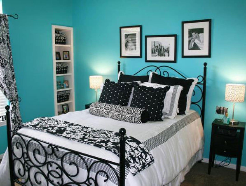 wandfarbe blau mit wandgestaltung schwarze bildrahmen-metallbett schwarz mit weißer bettwäsche und schwarzen kissen-gardinen weiß schwarz-eingebauter wandregal weiß